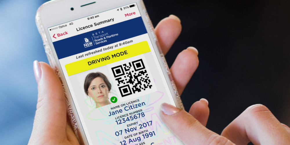 A woman holds her digital driver licence in her hands.